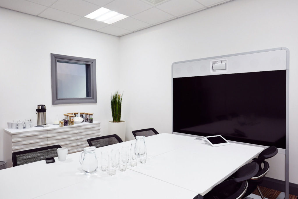 White private meeting room with large table facing a TV screen with refreshments on the table