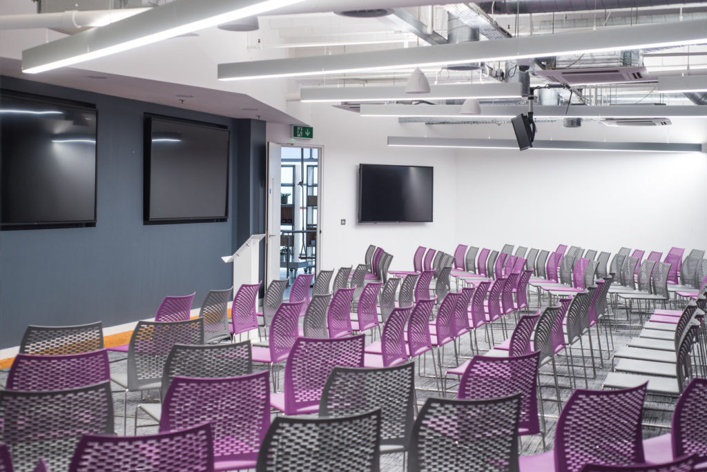 A large auditorium with purple and black netted chairs