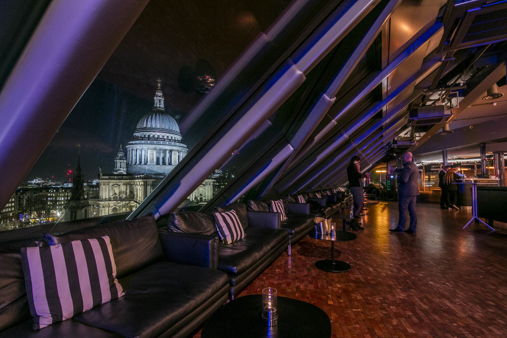 A covered rooftop lounge at night with views of St. Paul's Cathedral.