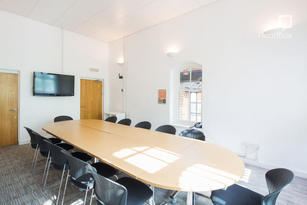 Bright spacious meeting room with wooden, oval shaped table and black chairs