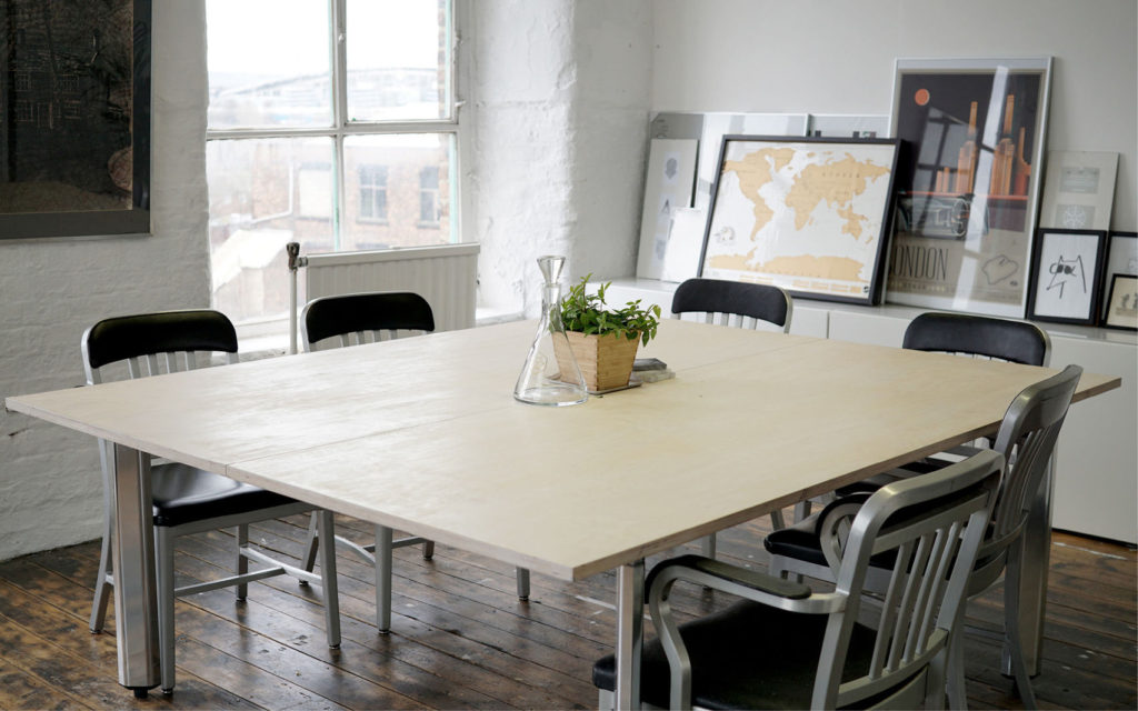 Small meeting room with square table and six black chairs with brick walls and framed pictures against the wall