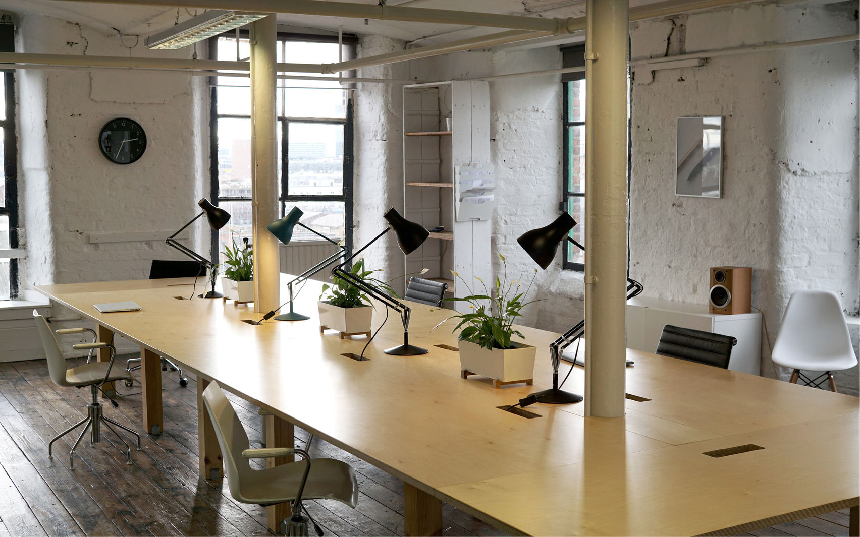 Industrial meeting room with large wooden table, shelving and shrubbery on the table with long windows