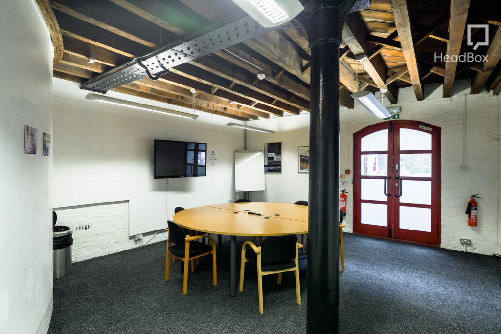 Industrial looking private room with white walls and wooden beams on the ceiling with TV screen and round wooden table