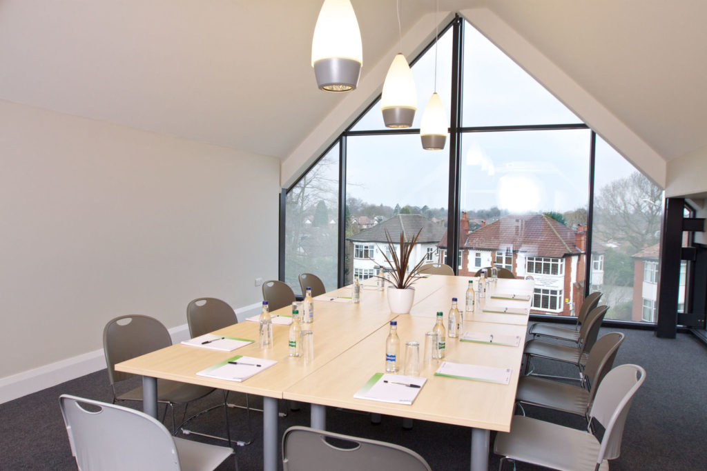 A bright spacious meeting room with a wooden table and large windows