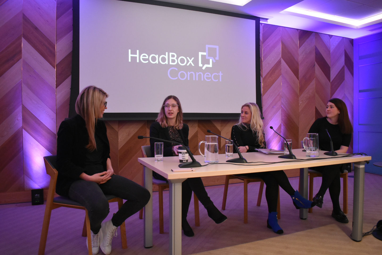 Panel event with four females sat at a wooden table with mics and glasses of water in front of a projector screen which says HeadBox Connect