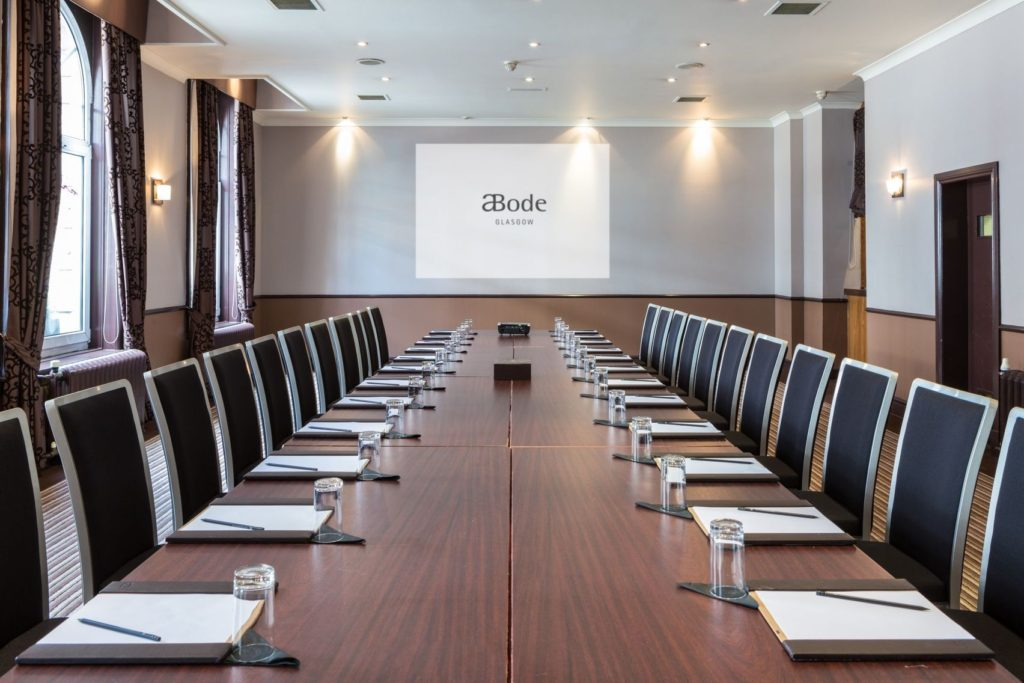 Meeting room with long wooden table with a projector screen at one end and natural light flooding the room