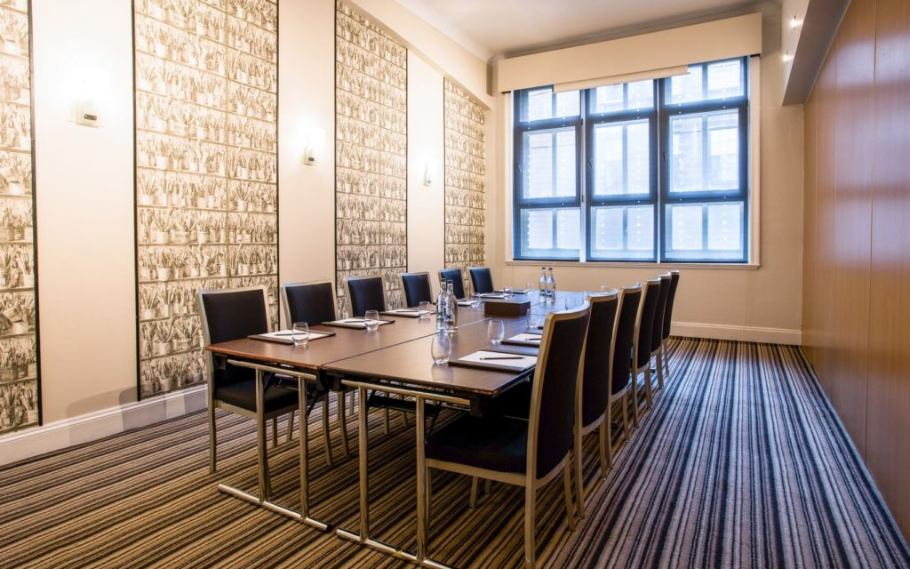 A private meeting room with wooden table with 10 chairs, white lighting, striped carpets and a large window