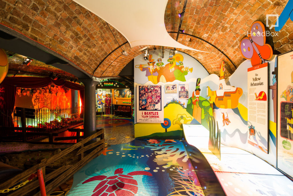 An underground venue with curved walls and bright coloured walls decorated with The Beatles
