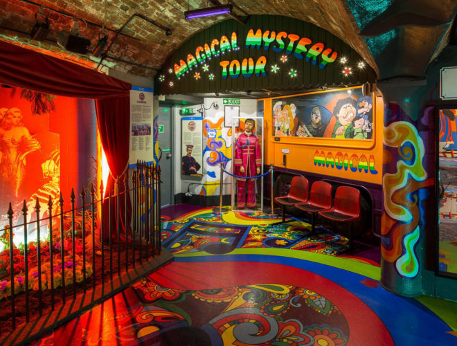 An unusual venue hire Liverpool. Inside of The Beatles Story. There is an arch which reads magical mystery tour that is surrounded by bright colours.