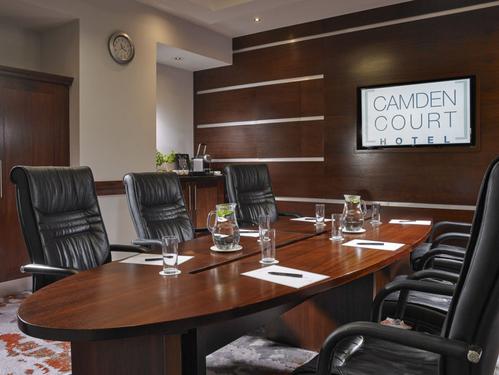 Boardroom with leather chairs around a wooden table facing a screen with glasses of water on the table