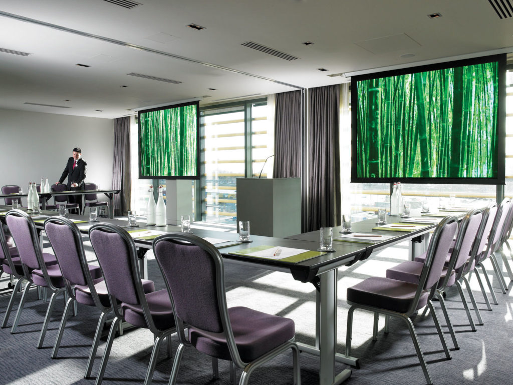 meeting room with u-shaped table layout with metal chairs facing a screen and windows letting in natural light