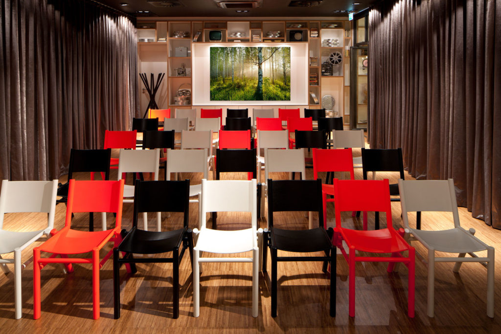 Black, white and red chairs set out in conference style with drapes either side and wooden floor