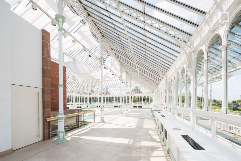 A large glass conservatory with a slanted ceiling