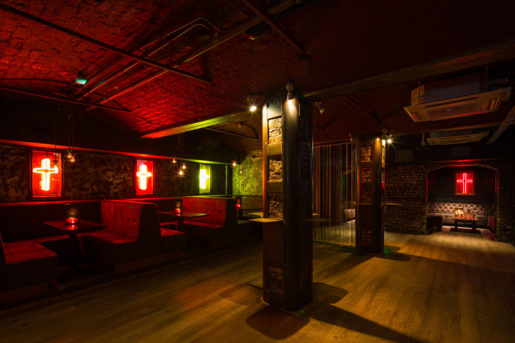 An underground bar in Liverpool that has curved exposed brick ceilings and neon lighting.