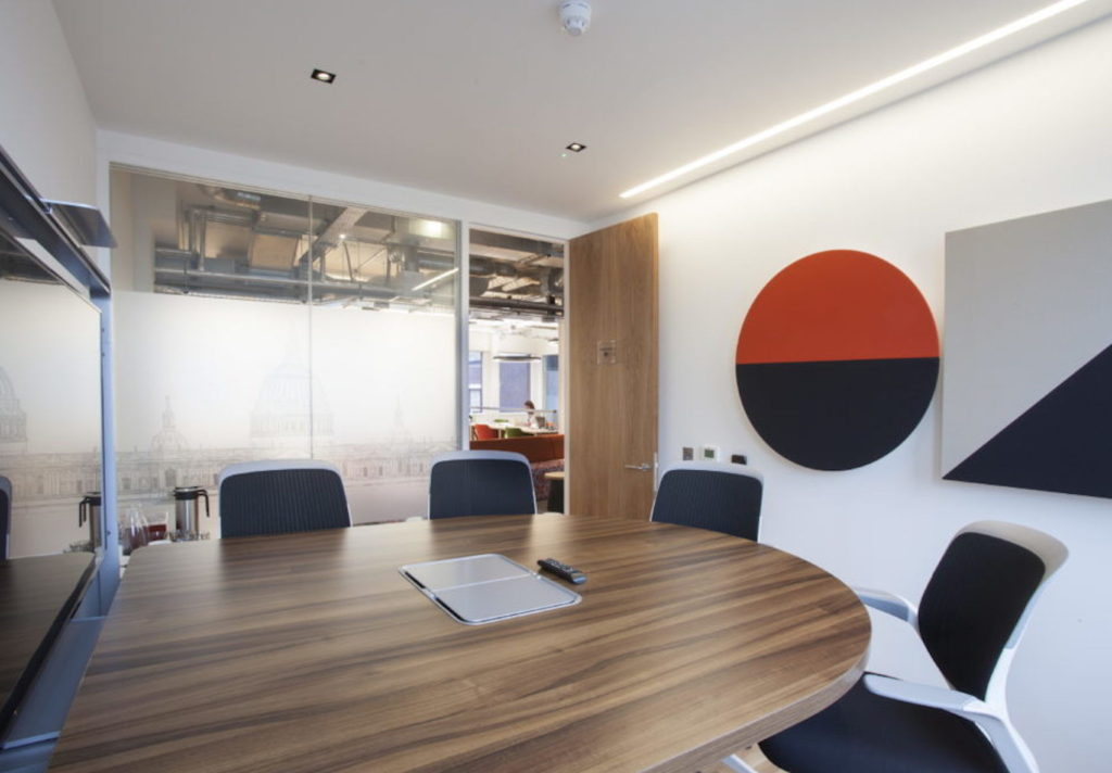 Small meeting room with glass panelled windows, wooden desk, three chairs and television screen