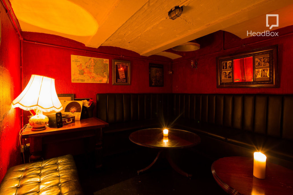 An underground speakeasy in Bristol which has dark red walls and is decorated with antiques