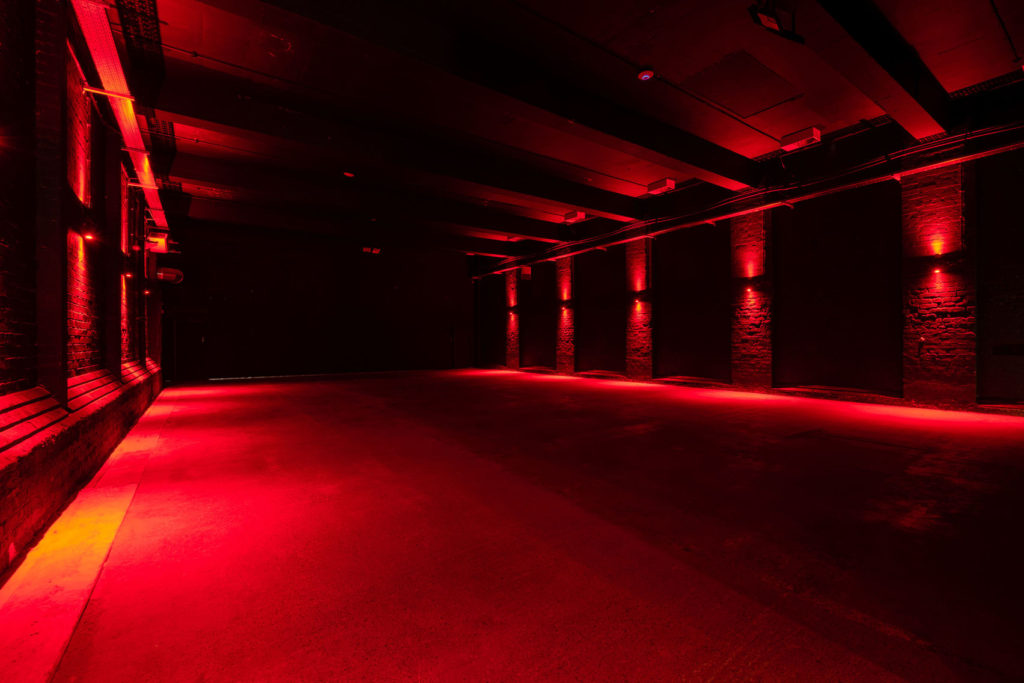 An empty underground warehouse venue. A large rectangle space that is lit up with red lights. An unusual venue hire Liverpool