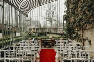 Conservatory party space with red carpets and white chairs