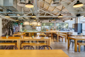 open food hall with wood tables.