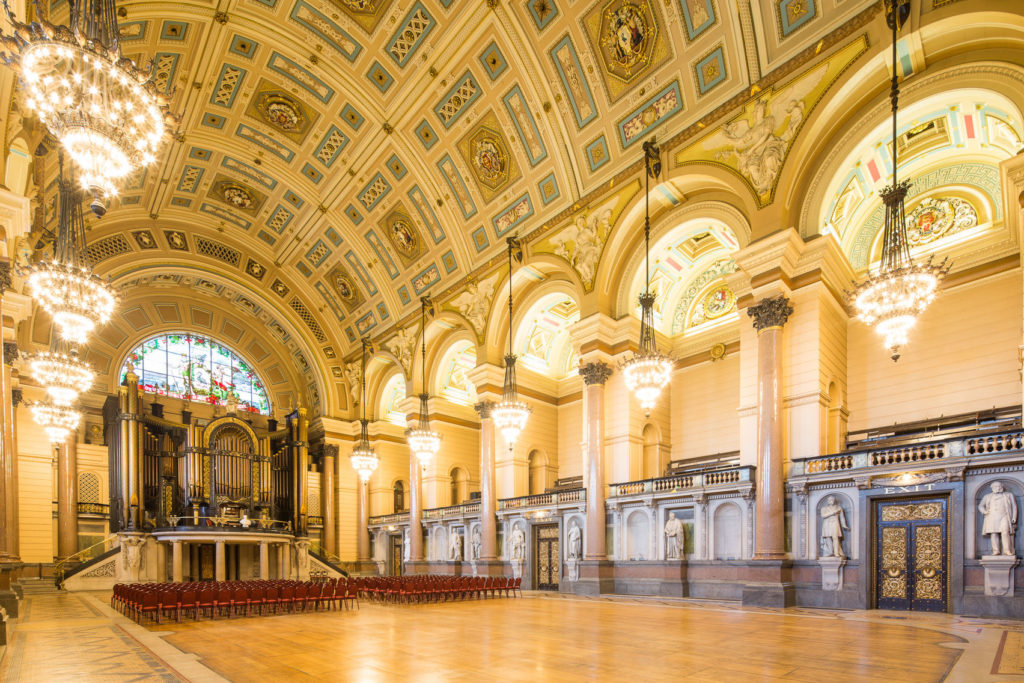 A huge grand hall in Liverpool. The venue has curved ceilings with are ornately painted and large chandeliers hanging from the ceiling