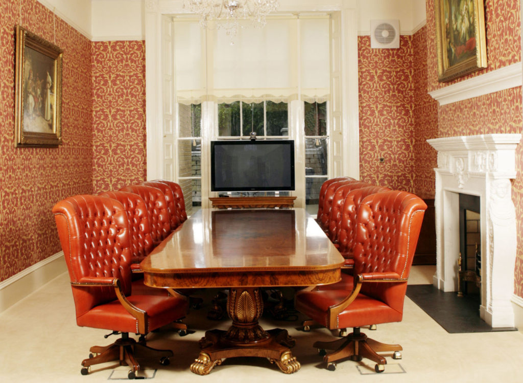 small meeting room with wooden table and eight leather chairs with TV screen, chandelier and fireplace
