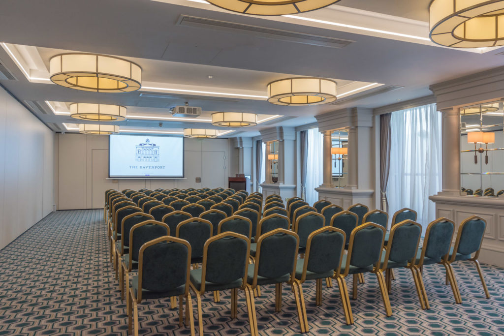 spacious meeting room with chairs set out conference style facing a screen