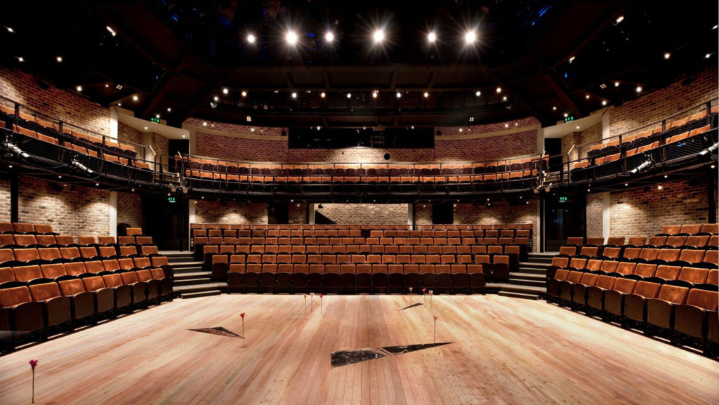 A large, curved amphitheatre in Liverpool with exposed brick and rows of seats