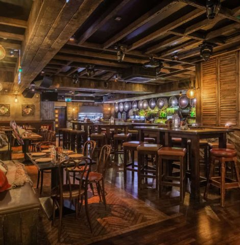 mexican bar with high tables and chairs with leather booth seats and a bar area