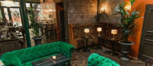 Trendy bar with bright green seating and exposed brick walls