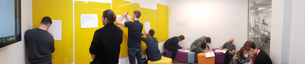 A group of people using whiteboards writing notes