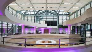 A large networking venue atrium with a circular mezzanine level and a glass roof