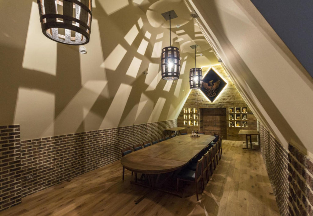 An unusual meeting room with a high pointed ceiling and barrels for lampshades