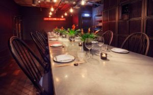 private dining room with long metal table with potted plants on it