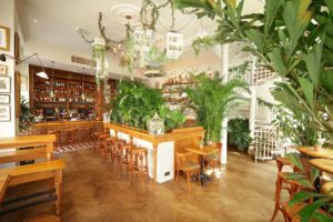 private room with wooden floor and furnishings and plants and shrubbery with a private bar