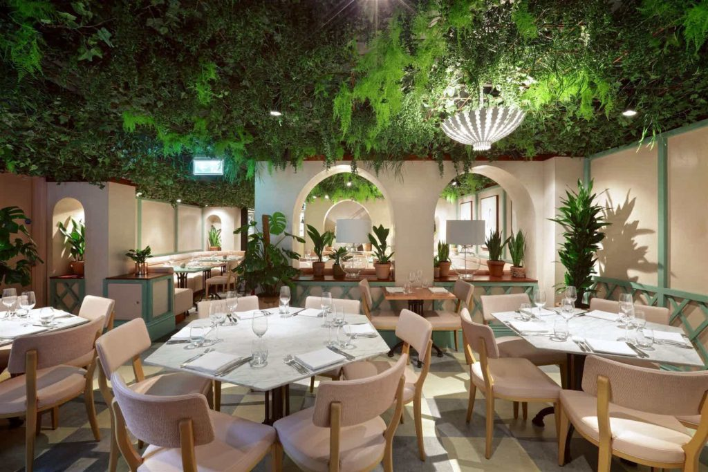 dining room with round tables with plants and leaves on the ceiling