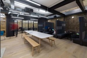 creative space with long wooden table and bench with booths and breakout areas