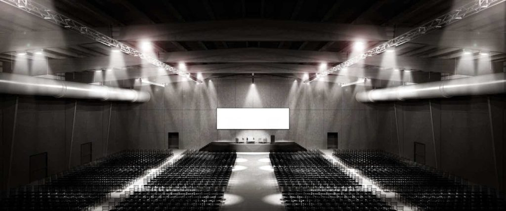 large conference room with rows of black seats facing a large projector screen