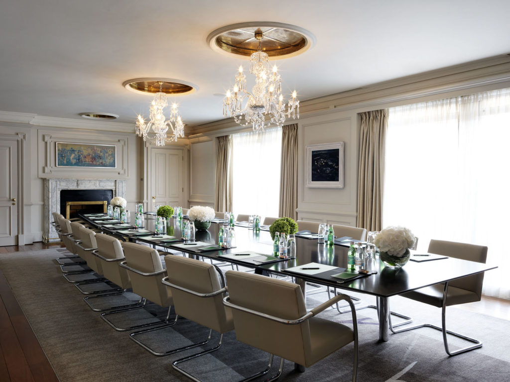 A white meting room with two large windows on the right wall. Their are two chandeliers in the middle of the room and a long black table surrounded by cream chairs