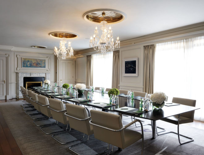 meeting room with long black table and cream leather chairs with flowers on the table and chandelier providing white light