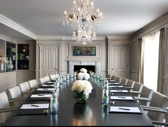A large meeting room that has white walls and a large black table in the middle and meeting pads on the table