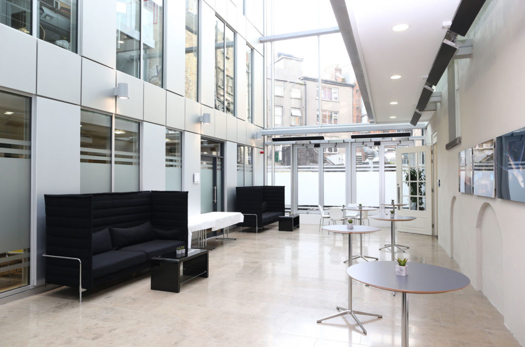 A large white reception area with glass ceilings and spotlights. There are two black sofas and 4 standing white tables