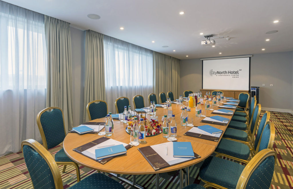 A large meeting room that has a long round table in the middle and is surrounded by blue chairs