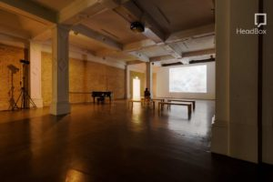 An industrial art gallery with exposed brick walls and polished concrete floor