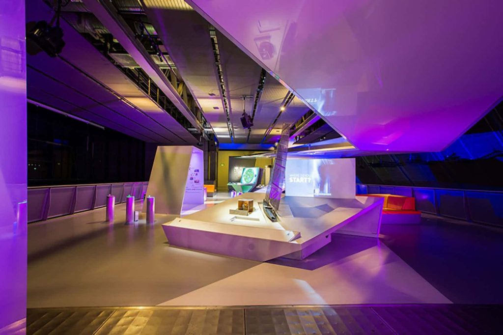 event space with interactive screens and pink lighting