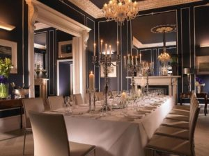private dining room with long table with candelabras and a hanging chandelier
