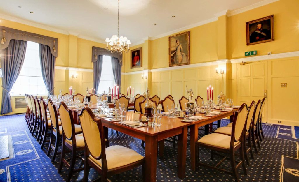 meeting room with long wooden tables and chairs, hanging lights and yellow walls