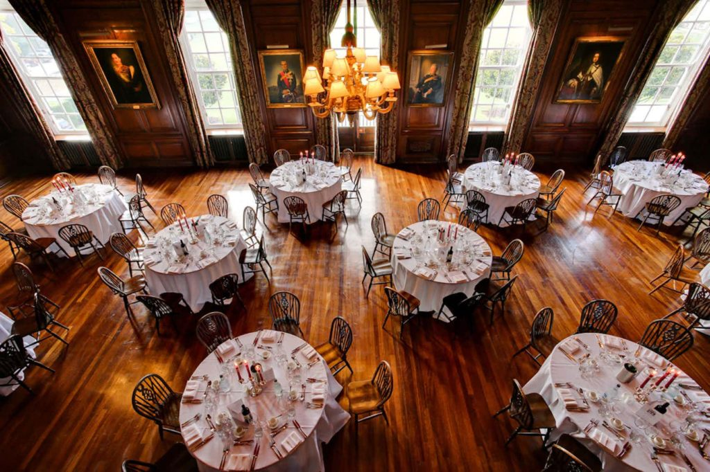 a function room with round tables, art on the walls, long windows and oak panelled floors