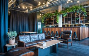 A laid back, small event venue which has leather sofas and green hanging plants