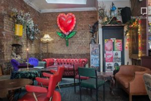 A pub venue with a mix of seating from sofas to chairs and a large heart on the back wall