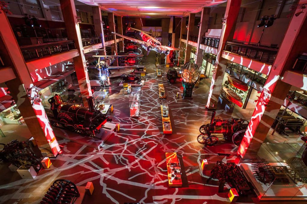 large event space with transport artefacts, red lighting and a balcony area